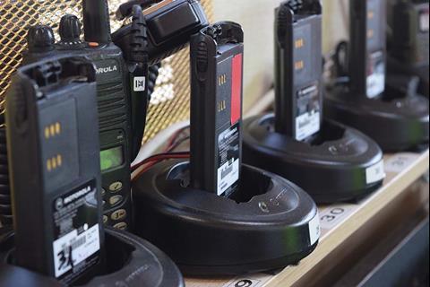 Several two way radios sitting on a shelf